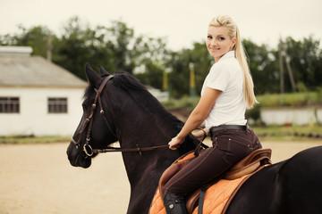 Image of happy female jockey on purebred horse outdoors