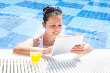 Woman Using Digital Tablet In Pool