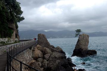 A couple walk along the rocky seaside in Portofino