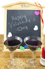 Valentine's decorated blackboard and two wine glasses