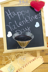 Happy Valentine's day on blackboard with hearts and a wine glass