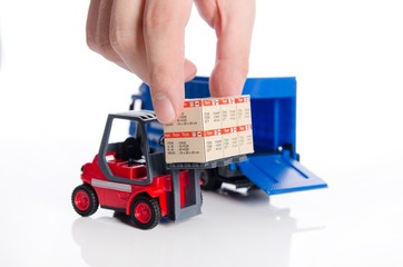 Hand taking boxes from forklift toy. Concept of international fr