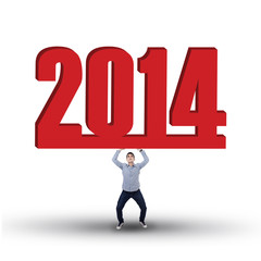 Casual businessman is lifting new year 2014