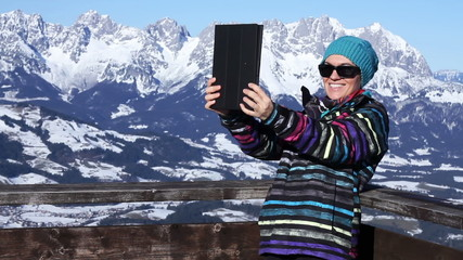 Happy young woman making selfie with tablet pc, Alps