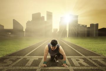 Fat person kneeling on running track