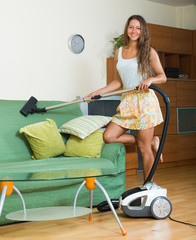 housewife  in skirt cleaning with vacuum cleaner