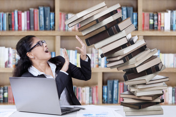 Worried student with fall books in library