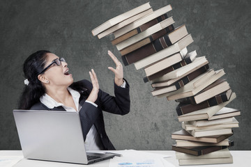 Worried woman holds a falling books