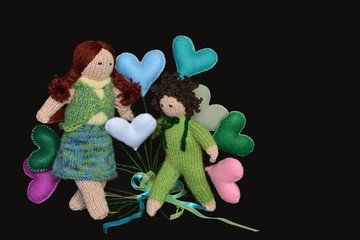 Handmade dolls, mother and child playing with coloured hearts