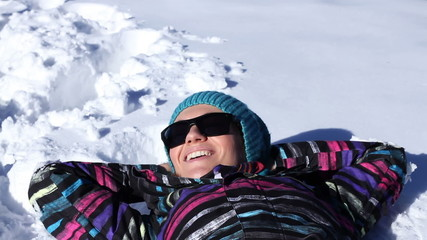 Happy skier woman lying in the snow of a high mountain