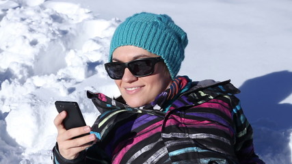 Happy girl lying in deep snow and texting with her phone