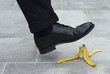 Businessman about to step on a banana skin - 77718033