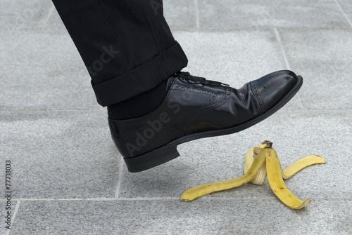 Leinwanddruck Bild Businessman about to step on a banana skin