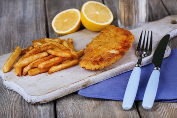 Breaded fried fish fillet and potatoes with sliced lemon and