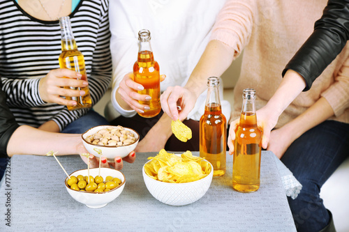 canvas print picture Friends hands with bottles of beer and snacks, close up