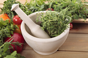 Fresh herbs with a mortar and pestle and vegetables on a wooden