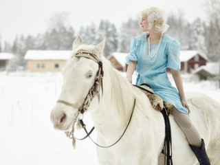 Attractive woman wearing blue dress and she riding a white horse