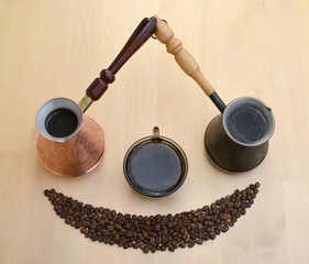 Two metal Turks, a cup about coffee and coffee grains on a light