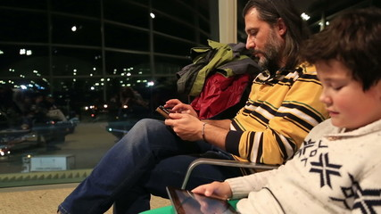 Father and son waiting at the airport