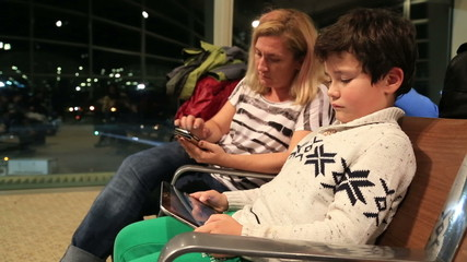Mother and her little boy waiting at the airport