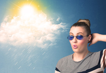 Young person looking with sunglasses at clouds and sun