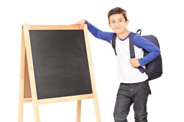 Schoolboy standing by a blackboard