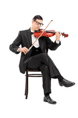 Classical musician playing violin seated on chair