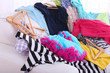 Leinwandbild Motiv Messy colorful clothing on  sofa on light background