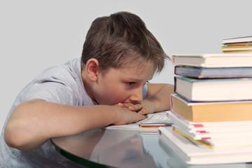 мальчик над домашним заданием положив подбородок на руки