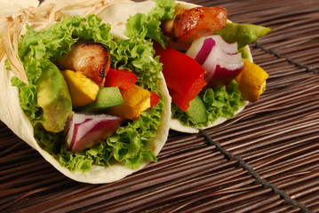Chicken and avocado wrap sandwiches on wooden woven mat