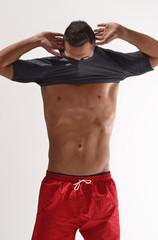 Deportista quitándose la camisa.Hombre atleta.