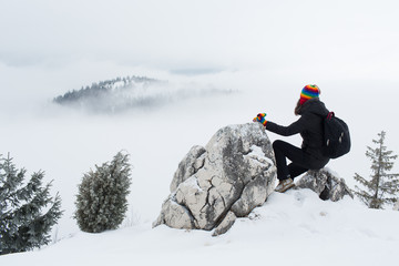 Side view of a woman in warm clothing resting on a rock in snowy