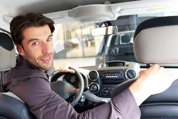 smarter junger Mann testet Auto im Autohaus