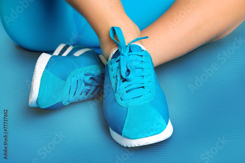 Female feet in turquoise sneakers on turquoise sports mat