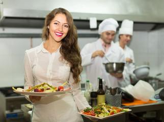Female waiter taking dish at kitchen