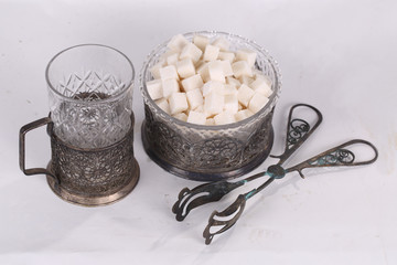 Sugar in a beautiful sugar bowl, tweezers and a glass in a coast