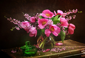 Peonies in a transparent vase and a green bottle