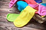 scattered multi-colored socks and laundry basket