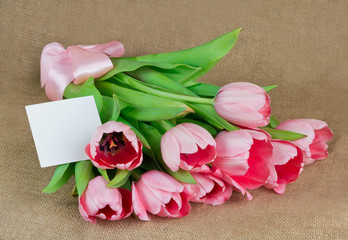 A bouquet of pink tulips with satin ribbon and little postcard