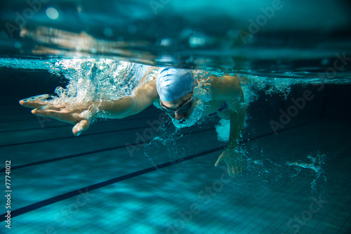 Male swimmer at the swimming pool.Underwater photo. - 77741012
