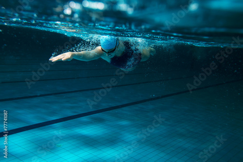 Female swimmer at the swimming pool.Underwater photo. - 77741087