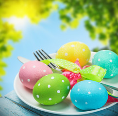 colorful easter eggs and cutlery on nature