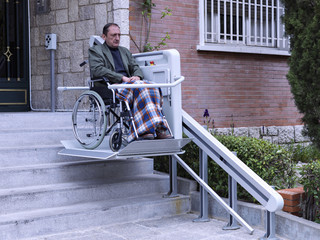 Man in wheelchair on a platform, climbing some stairs