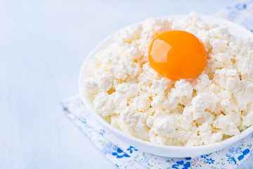 Cottage cheese with egg yolk in white bowl