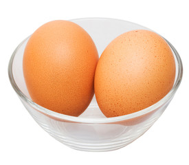 Two brown eggs in glass bowl