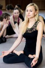 Yogi girl exercising, doing yoga pose sukhasana