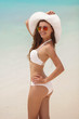 canvas print picture - Beautiful woman in a white bikini and hat on a tropical beach.