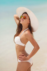 Beautiful woman in a white bikini and hat on a tropical beach.