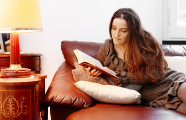 portrait of long hair girl absorbed in reading over sofa with ta