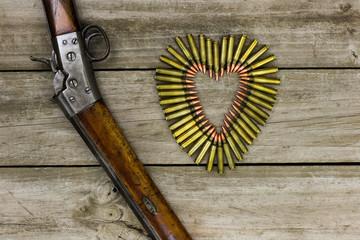 Gun by bullets in shape of heart